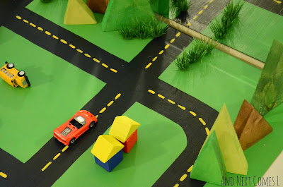 Block houses, cars, and homemade wooden trees on DIY road table from And Next Comes L