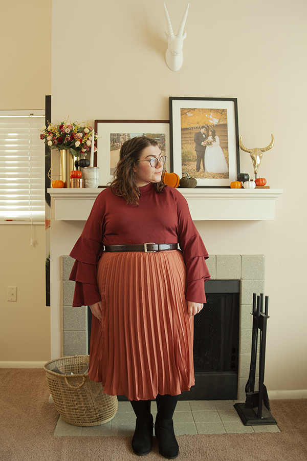An outfit consisting of a cranberry red three tiered bell sleeve blouse, rose colored pleated midi skirt, and black ankle boots.