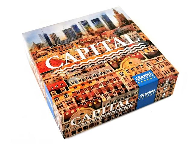 na zdjęciu pudełko gry capital z ilustracjami przedstawiającymi na pierwszym planie kamienice a na drugim wieżowce w warszawie