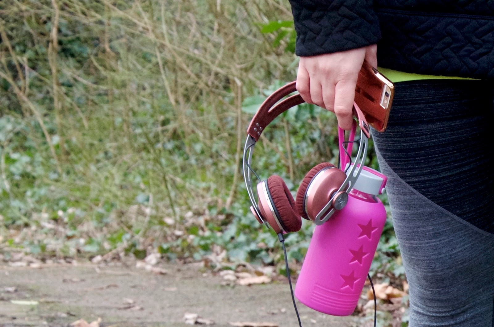 Pink headphones, pink glass waterbottle, grey leggings and rose gold iphone case