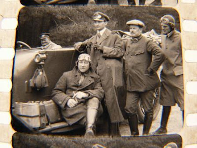 Airmen from The Great War posing by car with driver at wheel.