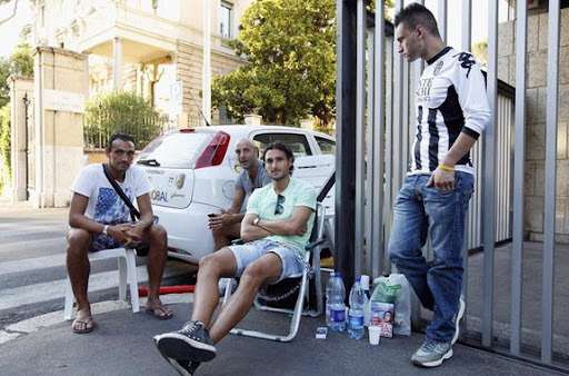Emanuele Pesoli sits on a chair after chaining himself outside of the FIGC headquarters