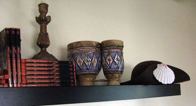 prateleira com livros, enfeites africanos e chapeu de peregrino de Santiago