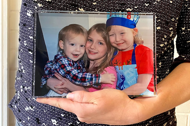 An image of a glass photoblock containing an image of 3 children being held in someones hands