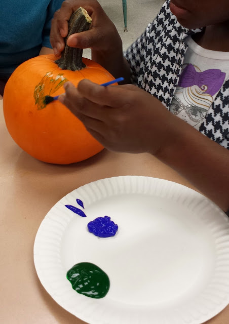 Photo of student painting a pumpkin.