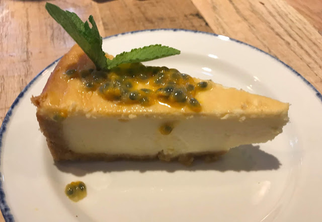 slice of mango and passionfruit cheesecake with sprig of mint
