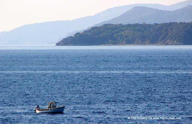 A tiny fishing boat in the sea with a mountain range in the distance.