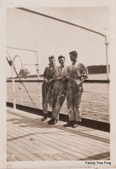 Three Men on a boat in boiler suits.  A bell is to their left.
