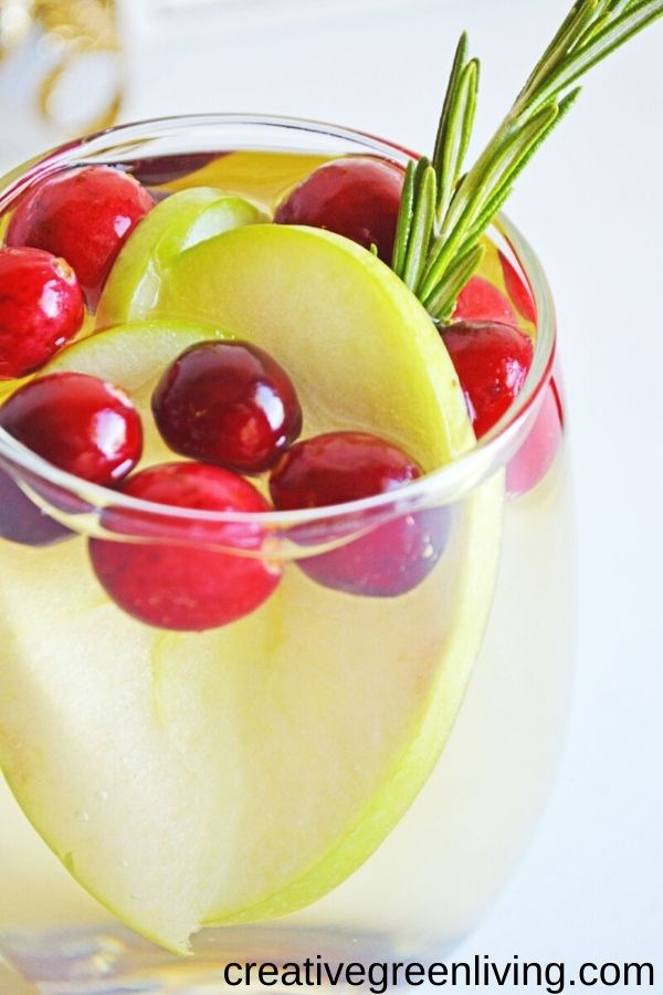 The best easy white wine sparkling sangria recipe perfect for winter. Garnish with apples and cranberries. This is a festive drink for Christmas or other winter holiday parties. Inludes single serving recipe and full pitcher recipe for a crowd. This is a dry, lightly sweet cocktail to serve by the pitcher.