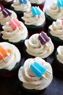 a bunch of sweet summertime cupcakes with swirls of cream cheese frosting and mike and ike popsicle toppers