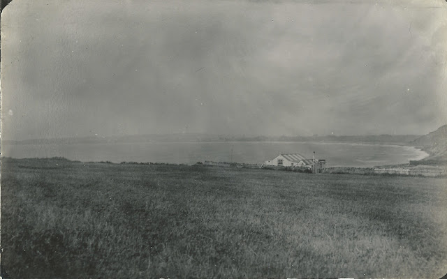 Field with Chalet in front of cove