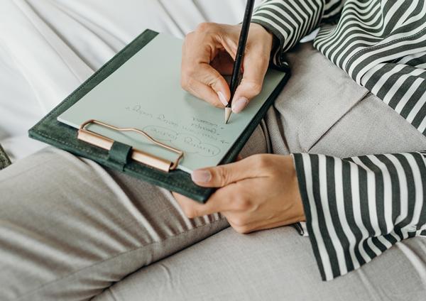 Mulher sentada escrevendo em uma prancheta