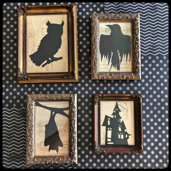 four gold vintage-framed black paper cut Halloween silhouettes on wall