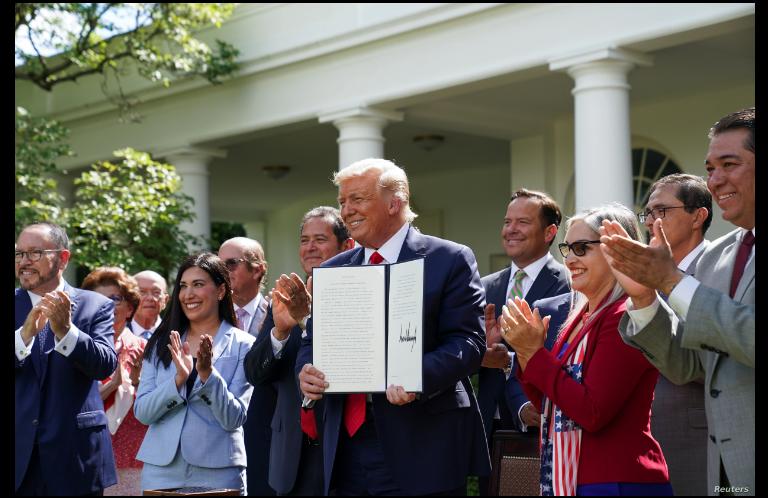 El presidente Donald Trump posa con el decreto sobre la Iniciativa para la Prosperidad Hispana de la Casa Blanca instantes después de firmar el documento / REUTERS