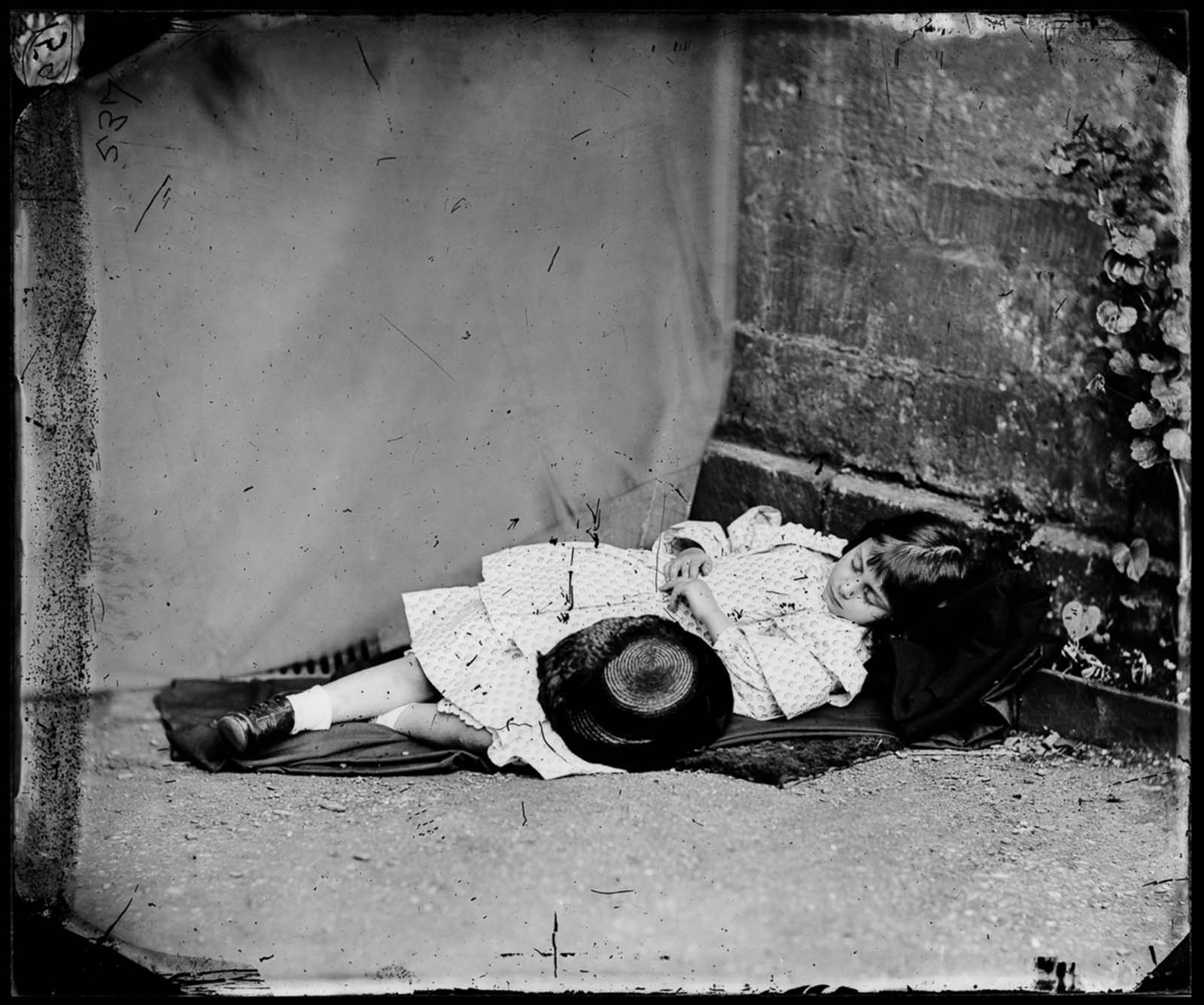 Alice poses in a feigned sleep. 1860.