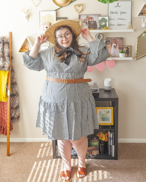 An outfit consisting of a straw sun hat with a black satin ribbon tied under the chin, a long balloon sleeve black and white gingham tiered midi dress, belted at the waist with a camel brown belt and camel brown slide sandals.
