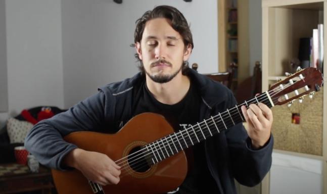 Pablo Romero Luis de olhos fechados tocando guitarra clássica.