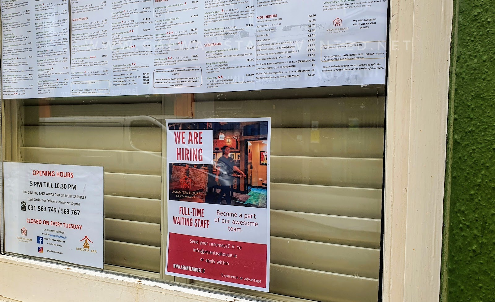 Asian Teahouse Galway pan-asia Restaurant window - with staff advertisement, opening hours sign - closed every Tuesday - and part of the menu showing.