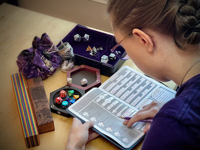 """Woman with braided hair and purple glasses is bent over a notebook with a character sheet for """"Veri Truestone."""" There are various dice around her, a rainbow set, a ceramic set, some resin sets and two metal dice in a tiny glass jar. There is a dice vault with rainbow colors, another with wood burning of a map, and then a dice bag with purple fabric. The dice are from Heartbeat Dice, Die Hard Dice, and Everything Dice. The rainbow vault is from Heartbeat Dice, and the map vault is from Deven Rue. The dice bag is from Tea & Tails. The rolling trays are from Wyrmwood Gaming and Die Hard Dice. And the book is the Adventure Journal from Table Titans."""