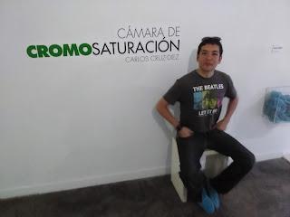 foto de Carlos Alvarez sentado en la entrada de la sala de Cromosaturación del museo Carlos Cruz Diez