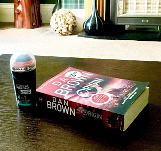 A small stubby black and silver rectangular bottle with a rounded top with a clear plastic lid with a silver label saying L'Oreal Mex Epxert Carbon Roll On in bright black font next to a rectangular book saying dan brown in white font on a brown rectangular table  on a bright background