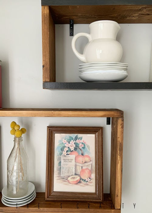 Vintage fruit prints from the thrift store displayed on wooden shelves.