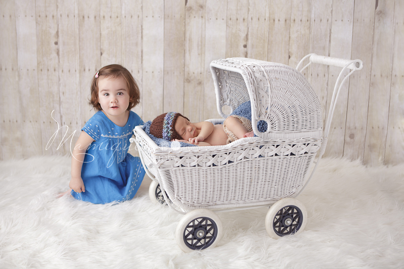 Todler girl with newborn baby brother in white wicker stroller