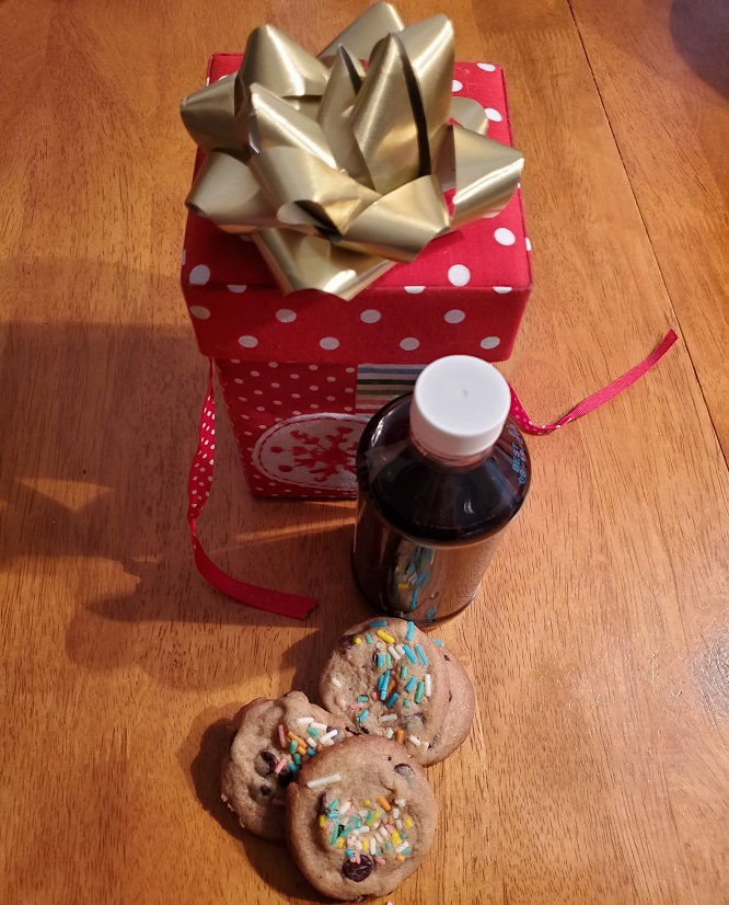 these are the chocolate chip cookies with real vanilla homemade extract in the background that is in a bottle and brown all ready for Christmas gift giving.