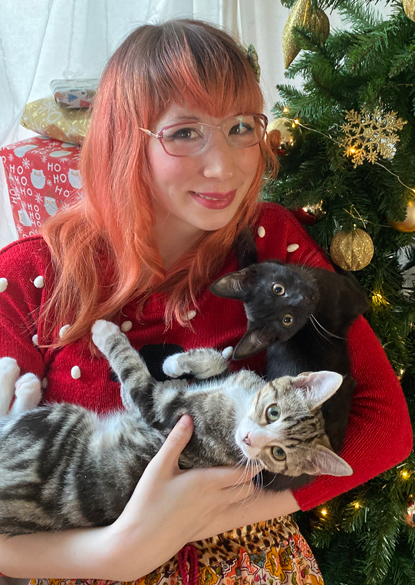 Woman with pink hair holding one black kitten and one tabby-and-white kitten