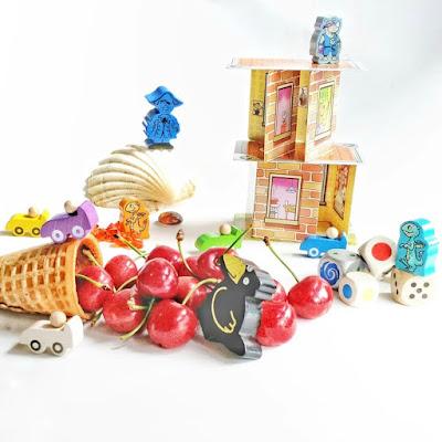 Un cono de barquillo relleno de cerezas rodeado de piezas de diferentes juegos de Haba