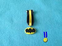 Medalla en fimo con el logo de batman: murciélago en negro sobre círculo elíptico amarillo