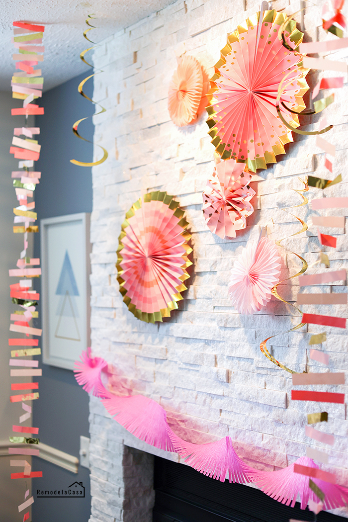 fireplace mantel decorated with paper fans and streamers