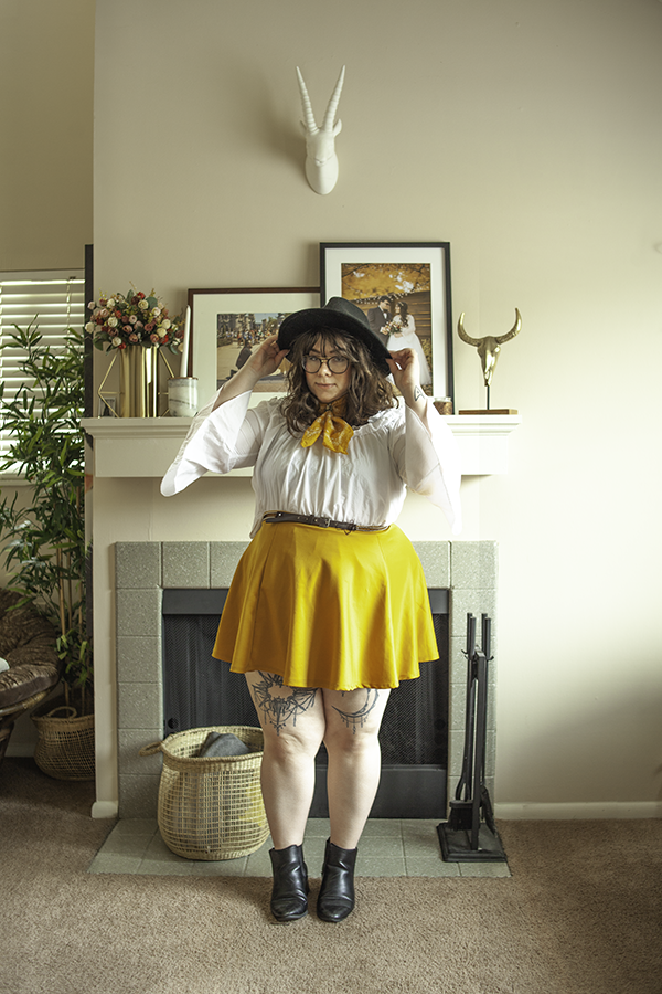 An outfit consisting of a black oversize fedora, yellow neck scarf, white ruffled off the shoulder blouse tucked into a golden yellow mini skater skirt with black heeled Chelsea boots.