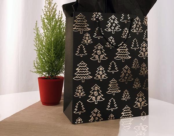 Sacola preta com desenhos natalinos em dourado ao lado de uma plantinha
