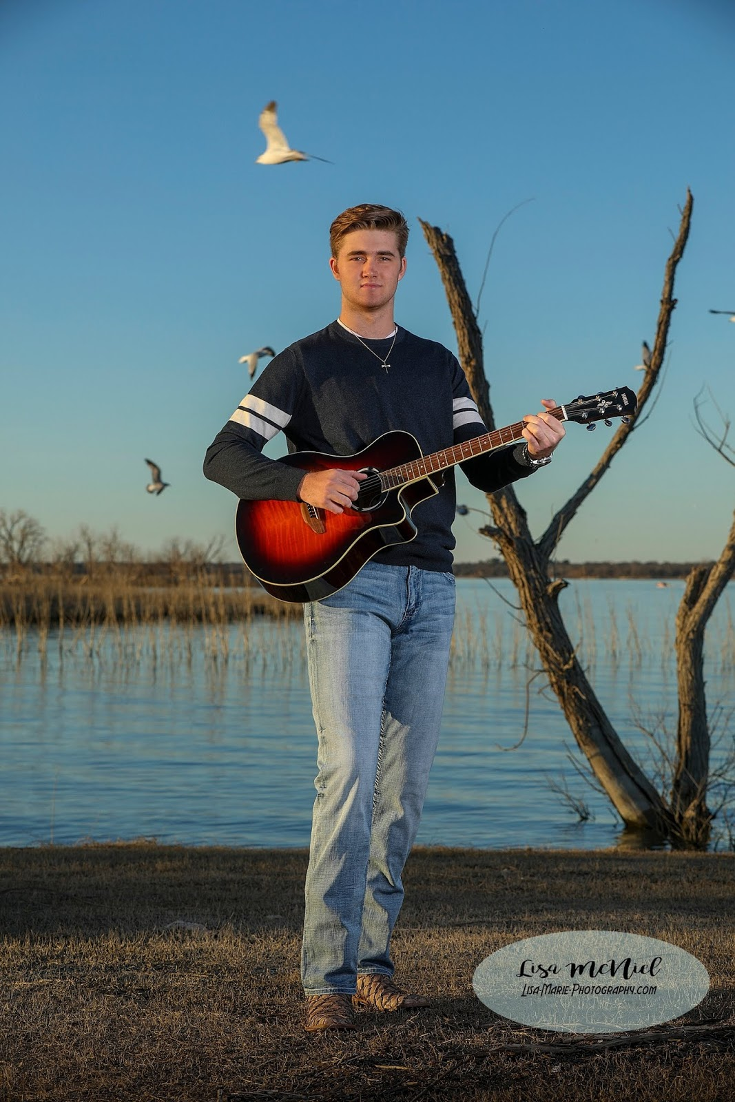 Handsome tall young man playing guitar in front of lake