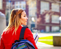 image of a young woman walking onto a college campus