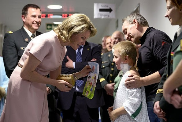 Queen Mathilde of Belgium speaks with a patient during a visit at the military hospital Koningin Astrid-Reine Astrid in Neder-over-Heembeek