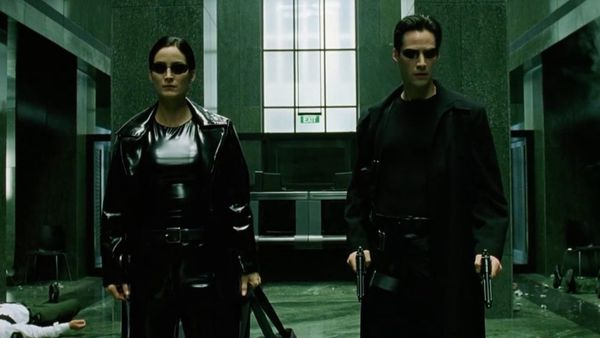 Trinity and Neo wearing black leather coats in the lobby in The Matrix