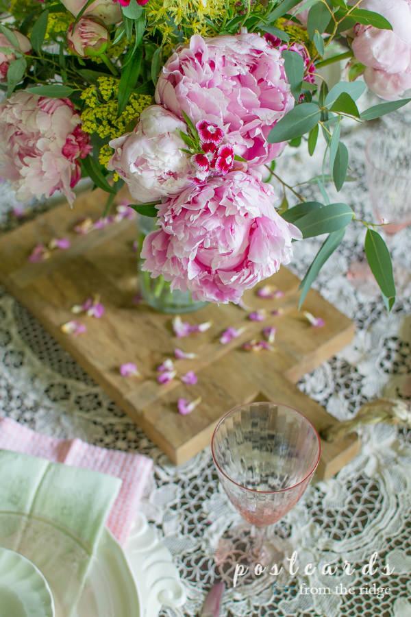 pink peony centerpiece on wood cutting board
