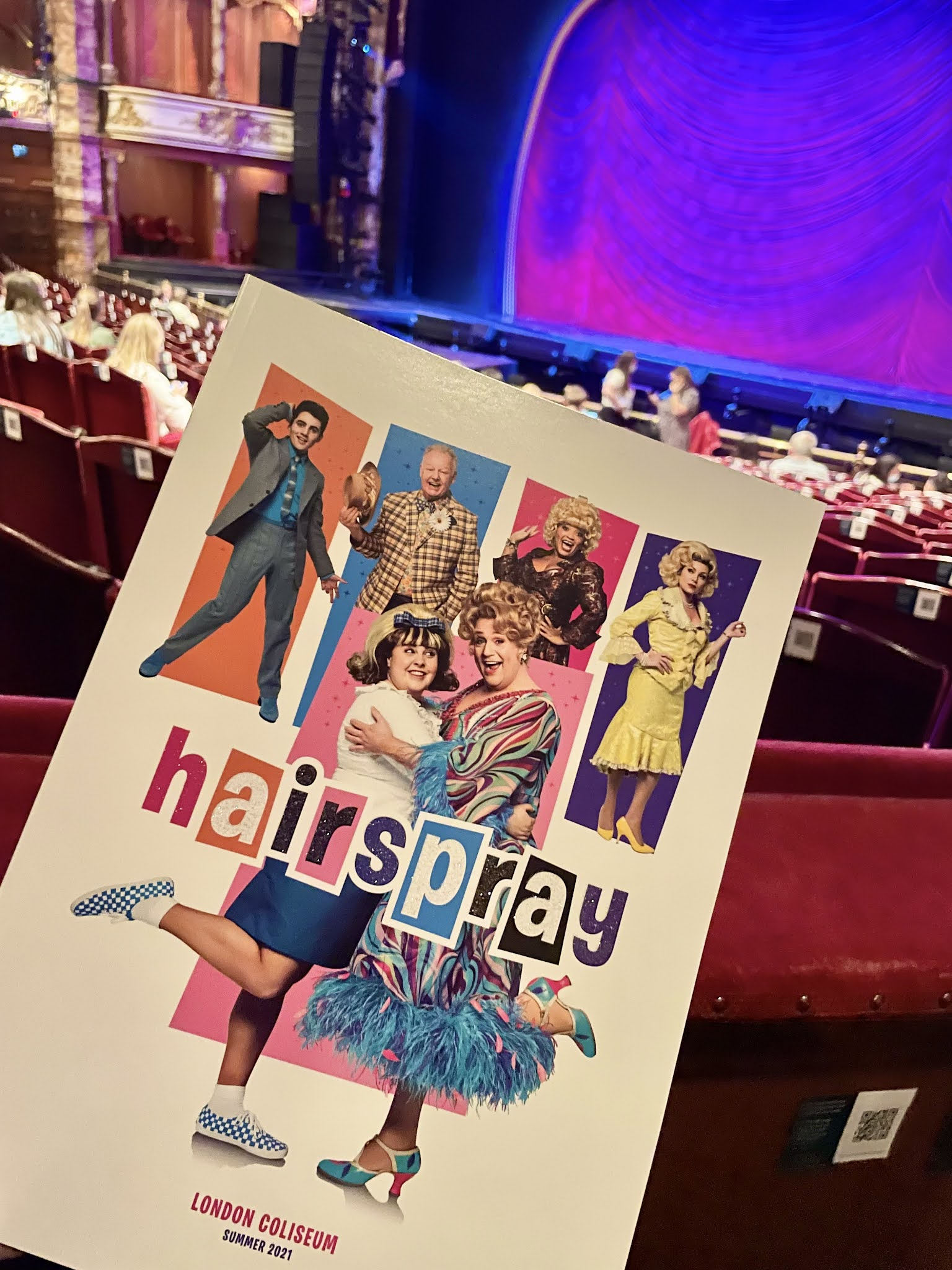 The programme for Hairspray the musical is building held up inside the theatre, the stage is lit up purple behind it.