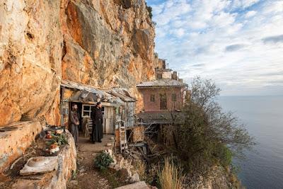 Μοναχοί κοιτάζουν έξω από το κελί τους, το οποίο κυριολεκτικά κρέμεται από τους βράχους στα Καρούλια του Αγίου Όρους. Φωτ.: Matt Fidler