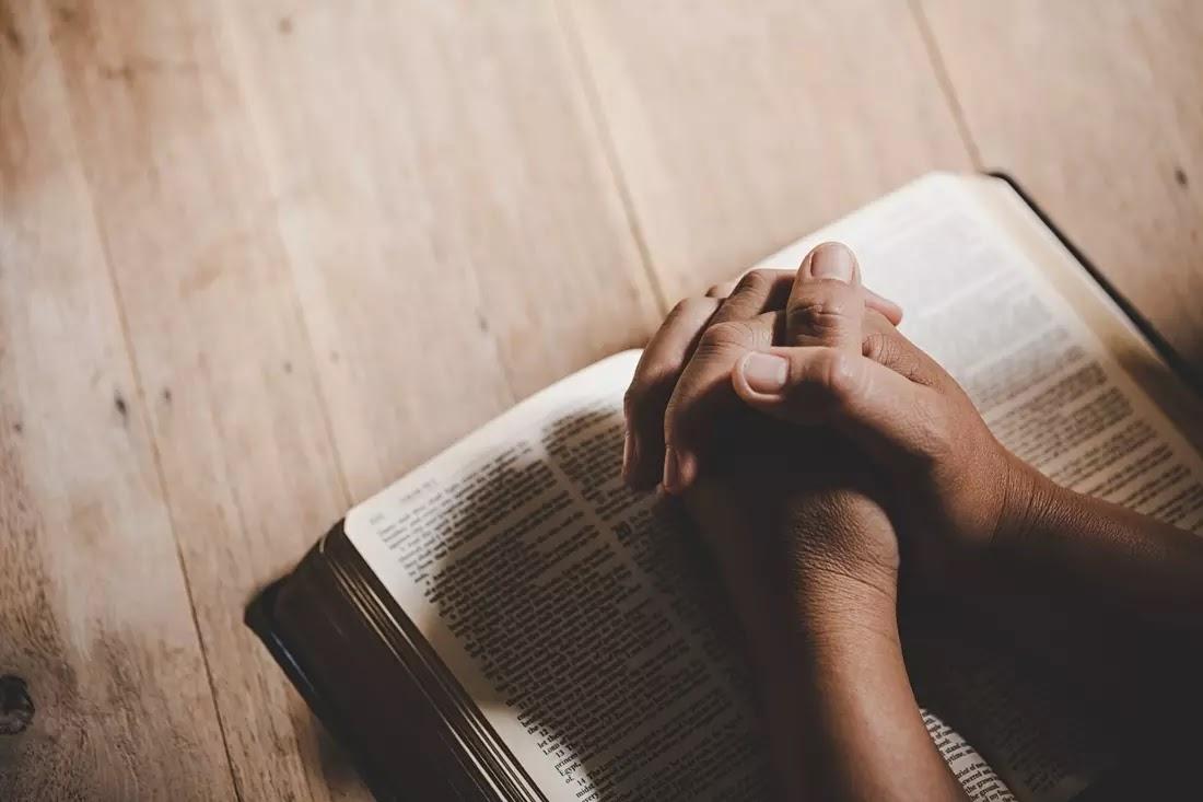 pessoa orando com uma biblia
