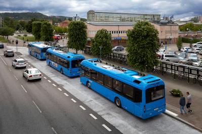 Tre blåa stadsbussar vid hållplatser utanför Kampenhof, sedda uppifrån.