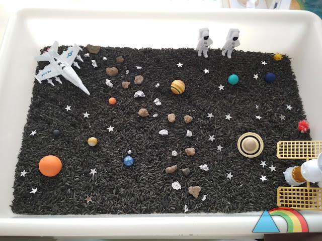 Bandeja con arroz teñido de negro, planetas del sistema solar en miniatura, piedras, confeti, naves y astronautas de juguete.