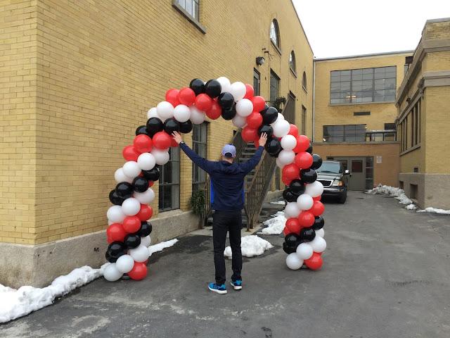 A 3 color spiral balloon arch near a big building