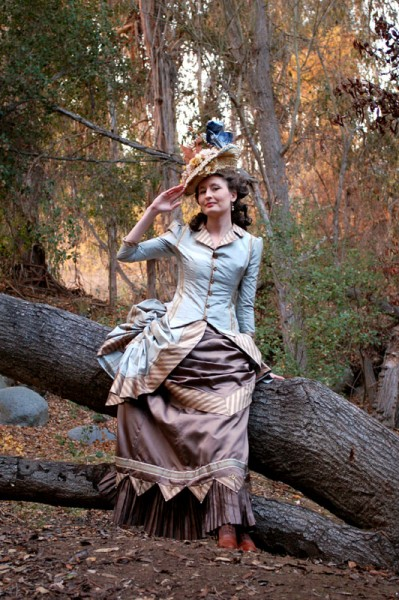 Woman wearing victorian dress with a bustle skirt, and top hat. Women's victorian costumes and clothing