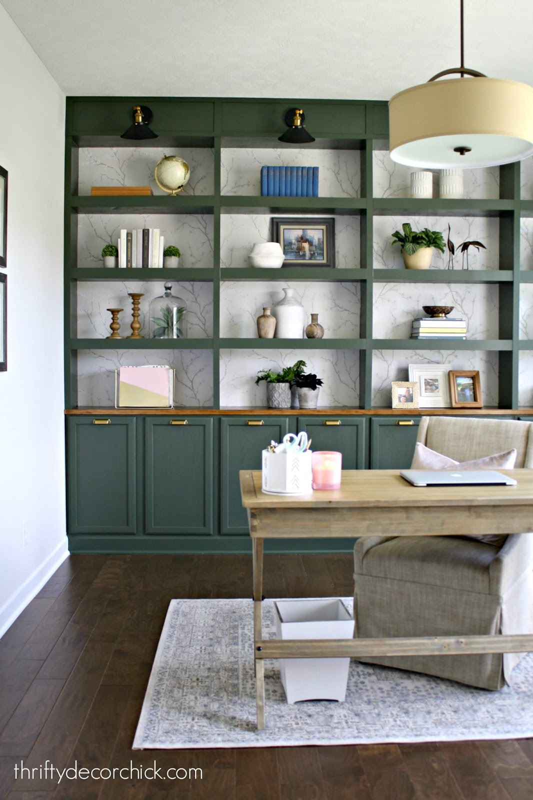Dark green built ins with wallpaper in office