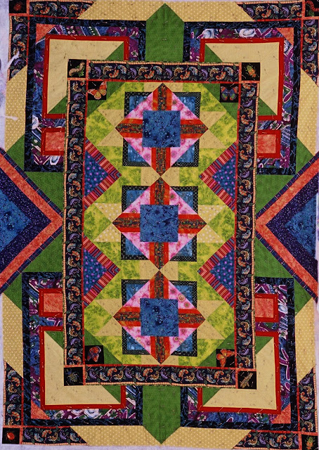 This quilt uses the same gecko fabric as an inner border and uses many fabrics in colors similar to the Lone Star.