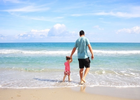 A father and daughter at the beach.