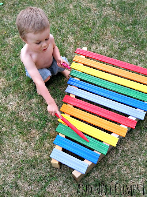 Kid playing on a homemade rainbow xylophone in the backyard